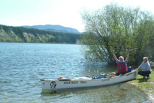 Buckwheat raises his paddle as Dottie Demark pushes him off on the start of his river journey to the Bering Sea at 11:36AM June 8th, 2006.